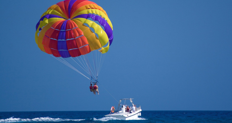 young adventurous people doing parasailing in the Ghoghla beach in Daman & Diu