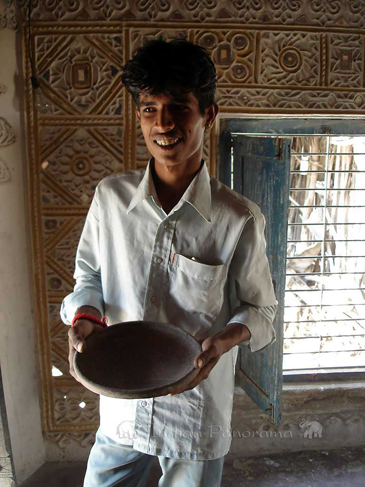 Villager proudly displaying handmade clay bowl