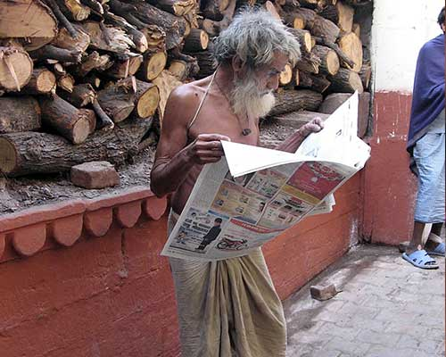 Pilgrim reading newspaper in Varanasi