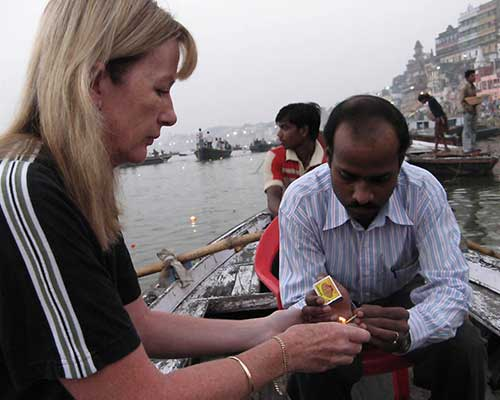 Lighting a candle for puja at dawn - Ganges